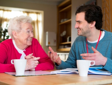 Older woman and younger man chatting over a cup of tea