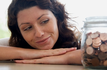 Woman looking at a jar of coins.